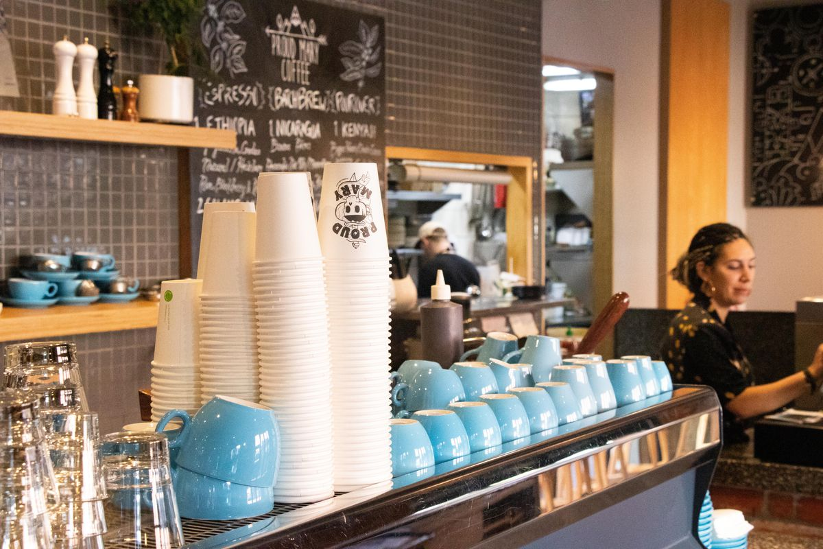 """A barista station with an espresso machine topped with blue mugs and paper cups that read """"Proud Mary"""""""
