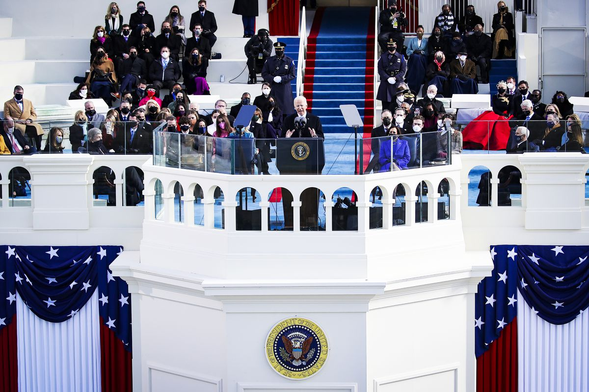 Joe Biden delivers his inaugural address on the Capitol balcony, surrounded by a few dozen people in masks.