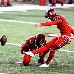 Utah Utes punter Ben Lennon (33) holds the ball as Utah Utes place kicker Jadon Redding (97) kicks a field goal as Utah and Oregon State play a college football game at Rice-Eccles Stadium in Salt Lake City on Saturday, Dec. 5, 2020.