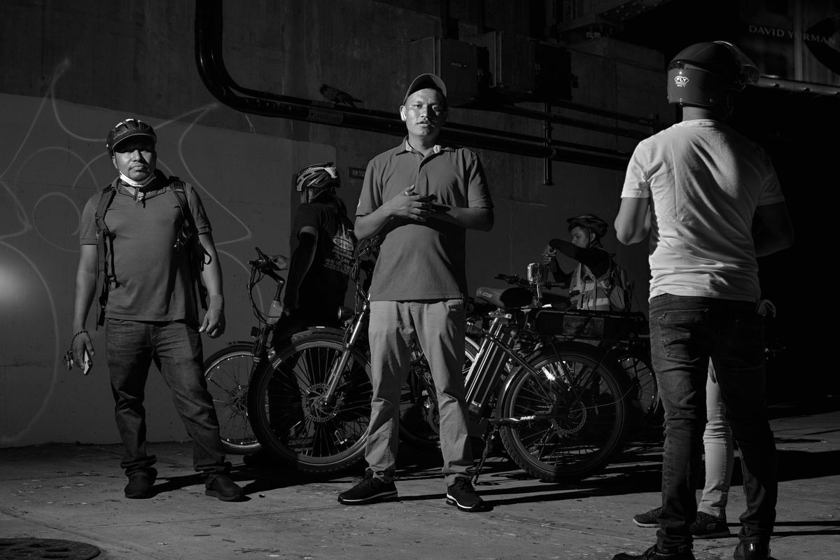 A black-and-white image of three delivery workers dressed in casual clothing, their bikes visible in the background.