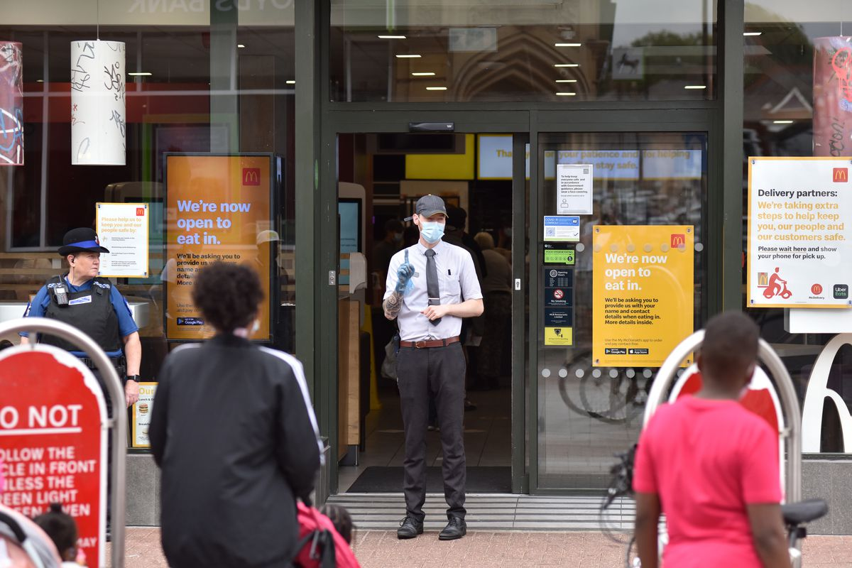 McDonald's staff in a mask stand outside a McDonald's restaurant controlling customer flow