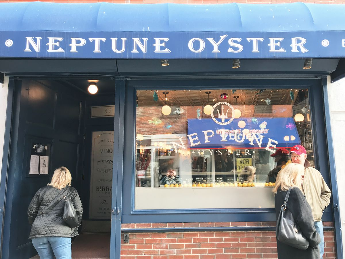 Several diners wait outside Neptune Oyster in the North End, huddled in fall coats under the royal blue awning.