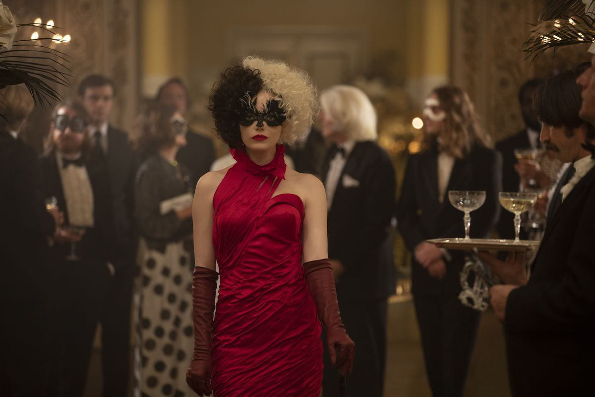 Emma Stone as Cruella de Vil in a red gown surrounded by party goers dressed entirely in black and white.