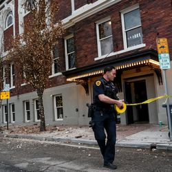 Salt Lake City police officer Henry Vadnais strings up police tape around fallen bricks outside a building at 400 South and West Temple after a 5.7 magnitude earthquake centered in Magna hit early on Wednesday, March 18, 2020.