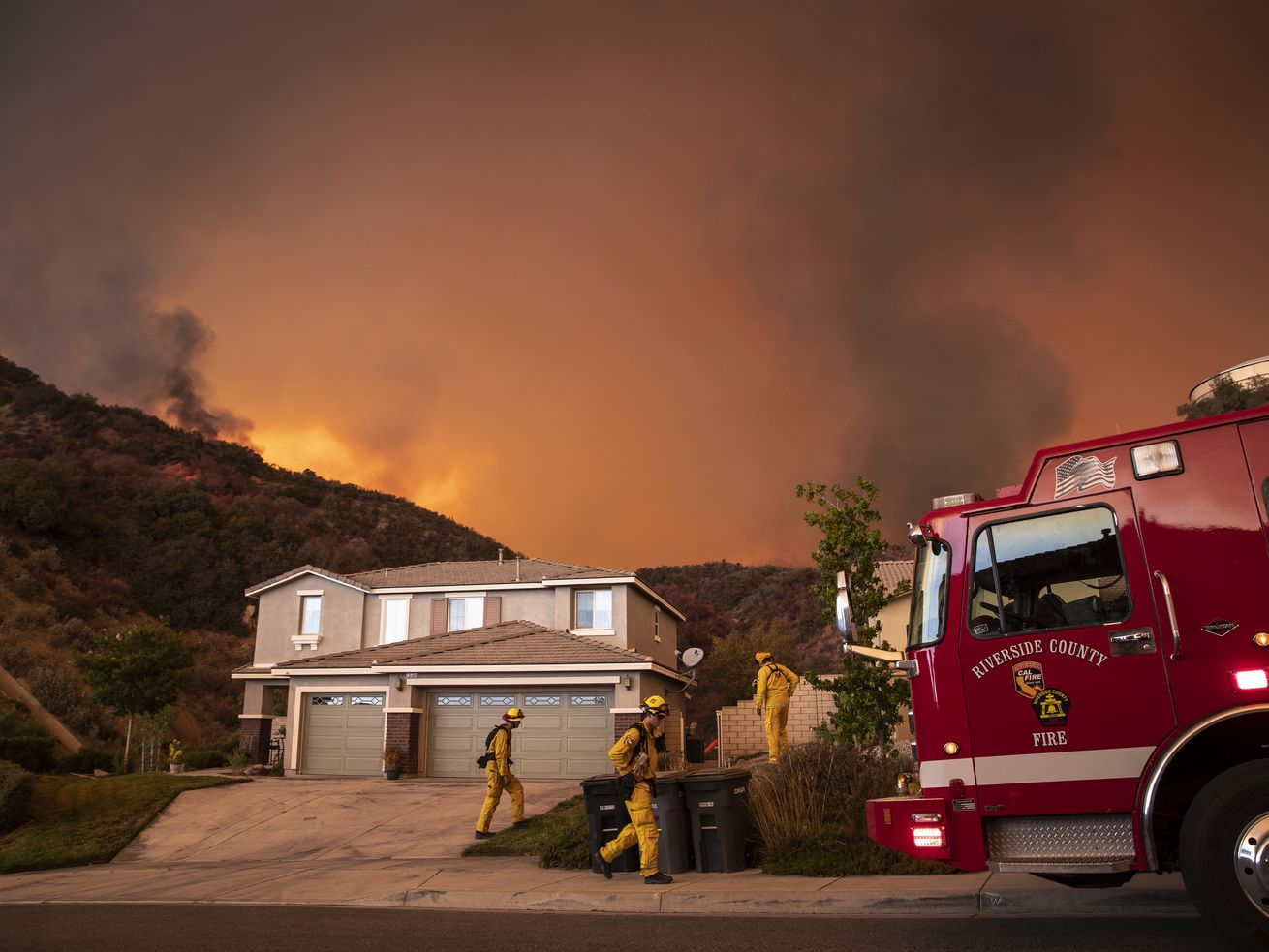 A suburban home with a three-car garage sits on a street with embers and the glow of fire in the background. A red fire truck sits in the photo's foreground.