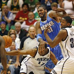 Utah's Ronnie Price (left) and C.J. Miles look for a loose ball past Denver's Nene as the Utah Jazz and the Denver Nuggets play.