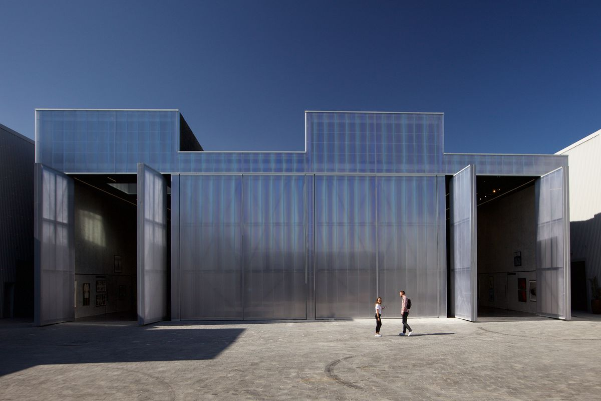 Front exterior of a polycarbonate clad warehouse with two large doors open on either end.