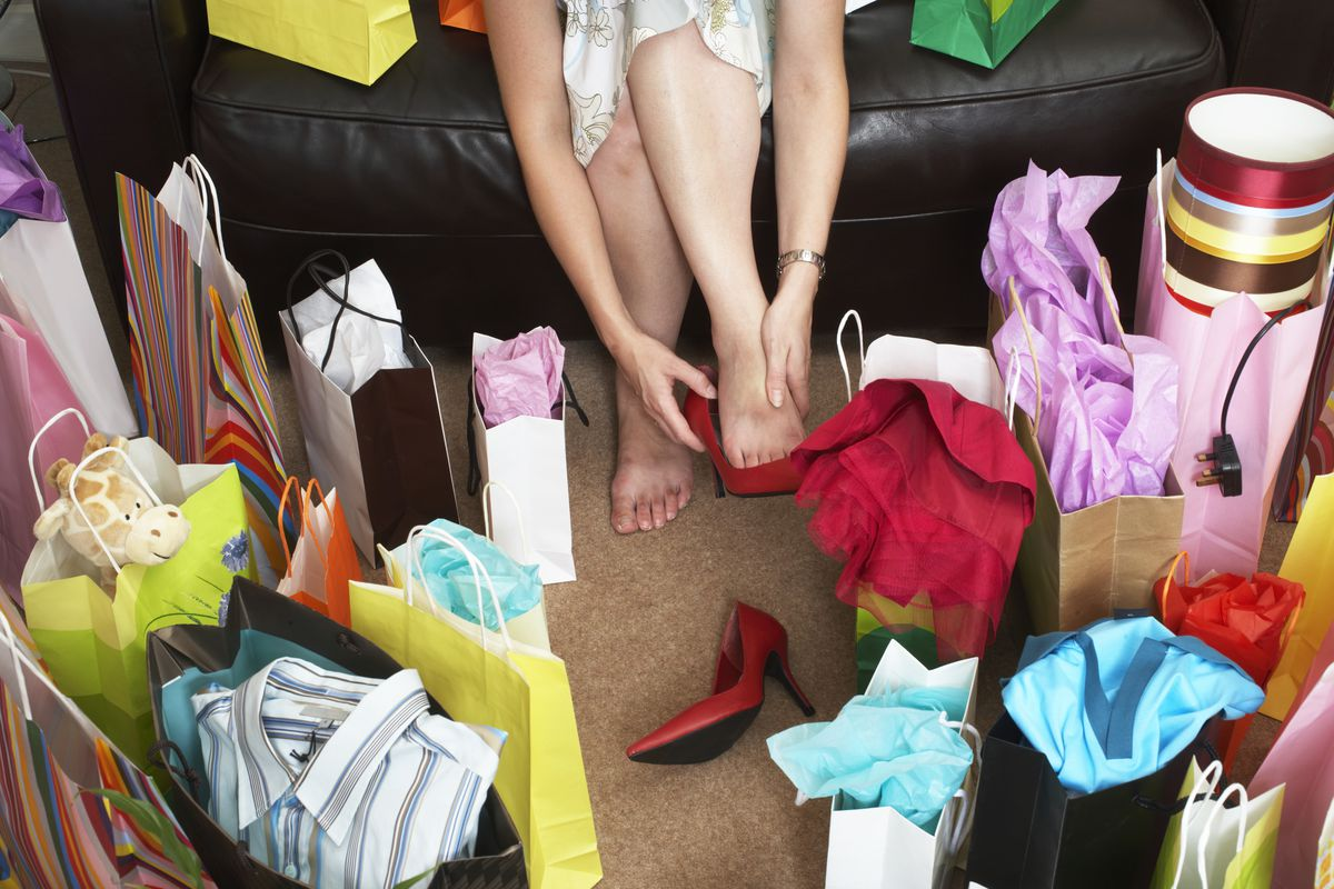 Woman with lots of gift bags rubbing feet