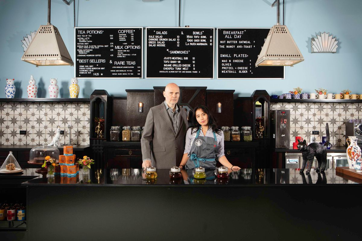 Smashing Pumpkins frontman Billy Corgan and partner Chloe Mendel stand behind a black counter inside a cafe space.