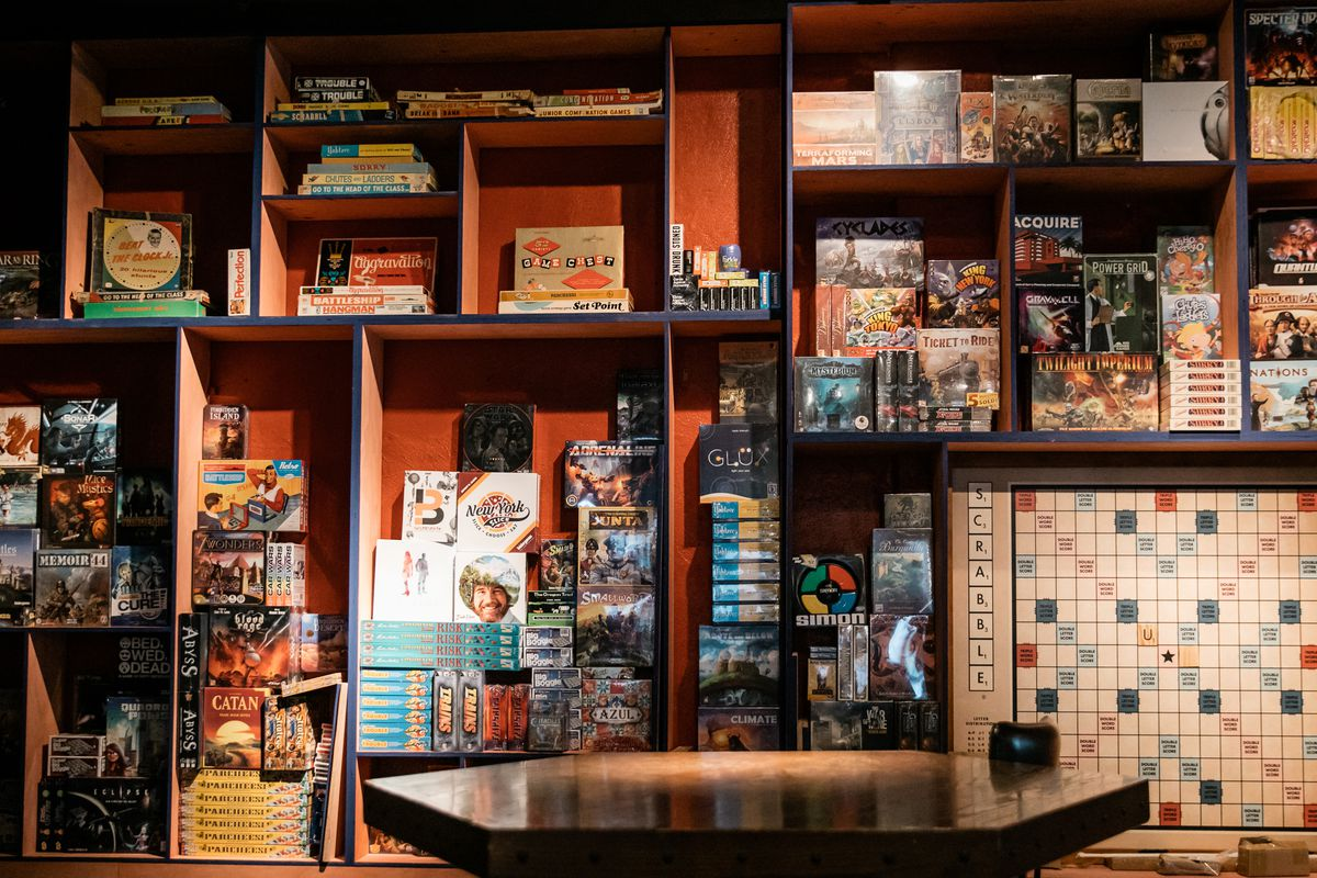A wall filled with different sized nooks stuffed with board games in a dark room.