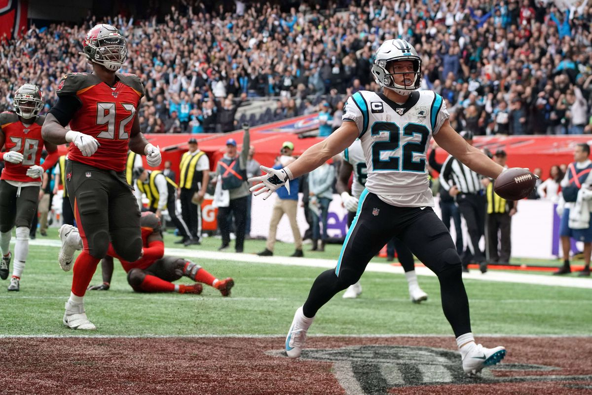 Carolina Panthers running back Christian McCaffrey is pursued by Tampa Bay Buccaneers defensive tackle William Gholston on a 25-yard touchdown reception in the second quarter during an NFL International Series game at Tottenham Hotspur Stadium.