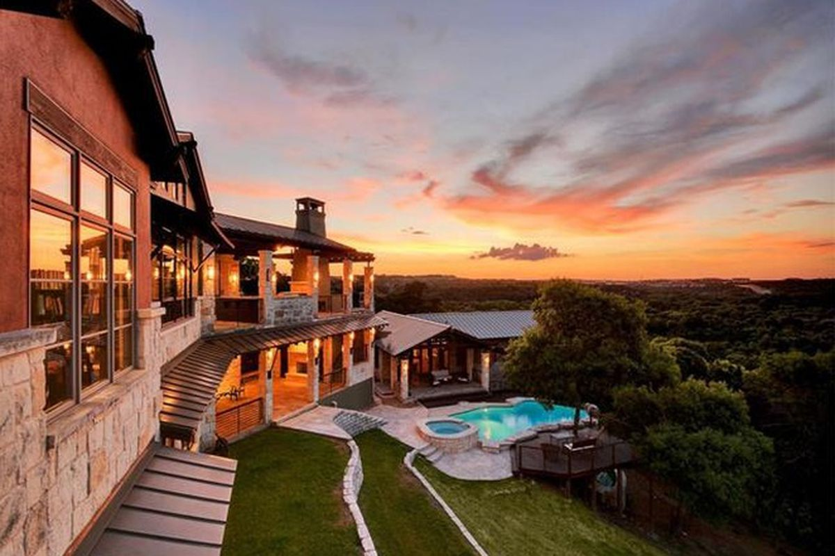 Exterior of a large house at sunset; house on left side, lots of windows, contemporary-traditional, pool below