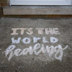 """""""It's the world healing"""" written in sidewalk chalk on the front porch of a home on North Ridge Boulevard near West Howard Street in the Rogers Park neighborhood during the coronavirus pandemic, Tuesday morning, April 7, 2020"""