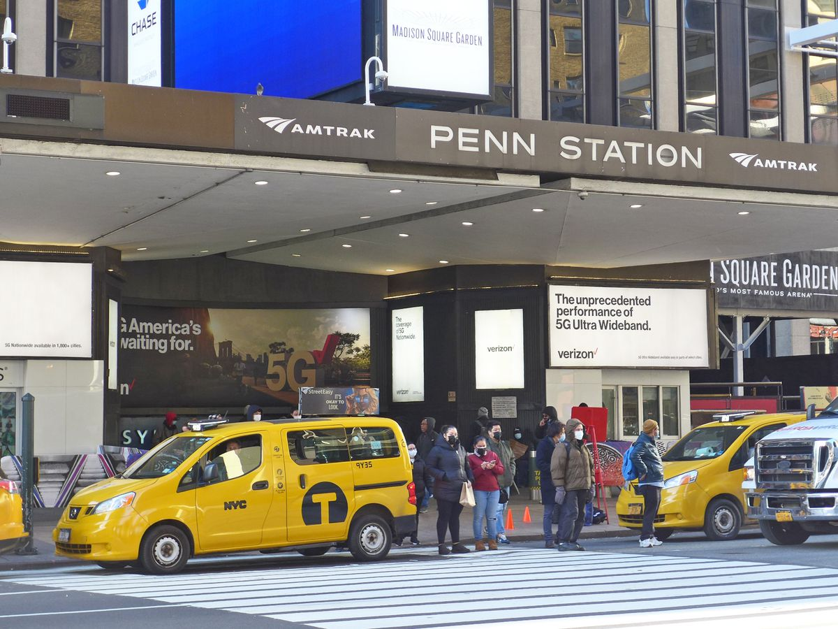 Cabs double parked outside the entrance to Penn Station with a crowd about to cross the street toward us.