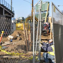 Worker replacing the fences along the Sheffield curb. Behind the worker, one of the utility excavations is visible