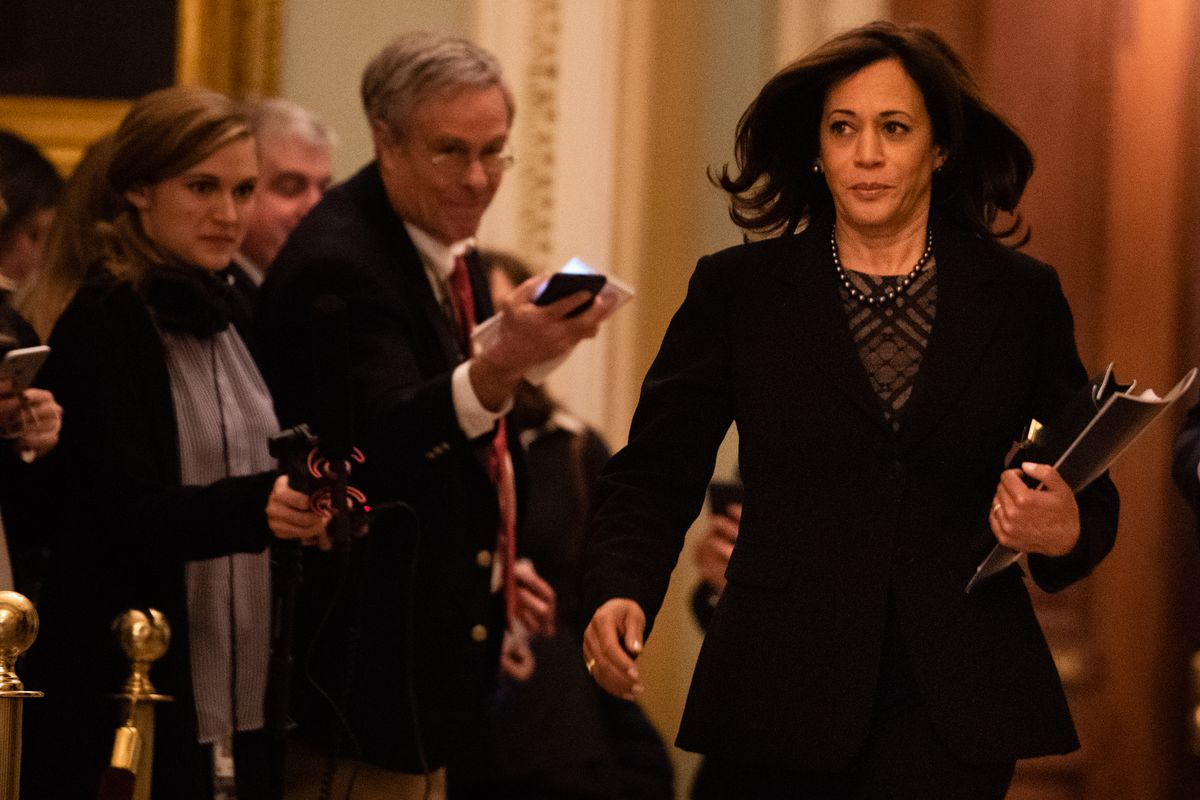Senator Kamala Harris walks past reporters holding out recording devices outside the Senate Chamber on her way to the impeachment trial.