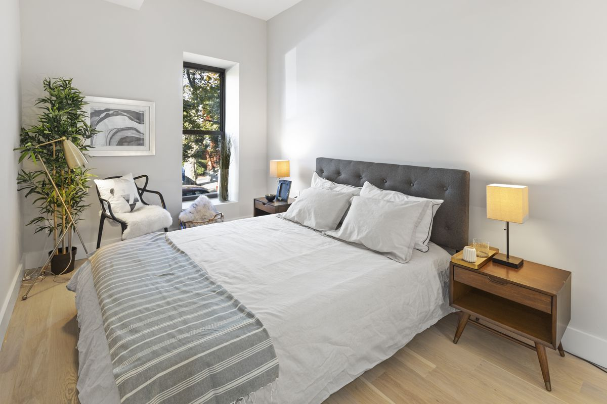 A bedroom with a large bed, light grey walls, one window, and a planter.