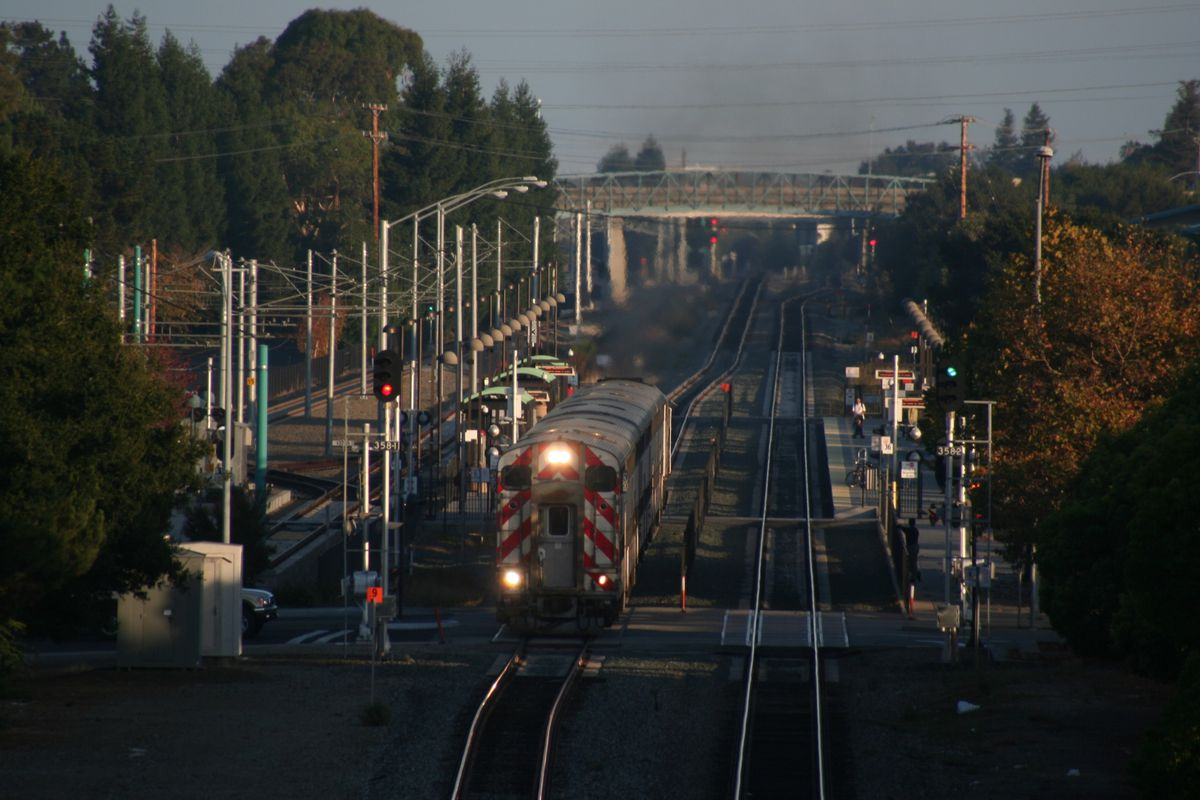 A Caltrain on the tracks, coming toward the camera, with trees and an overpass in the background.