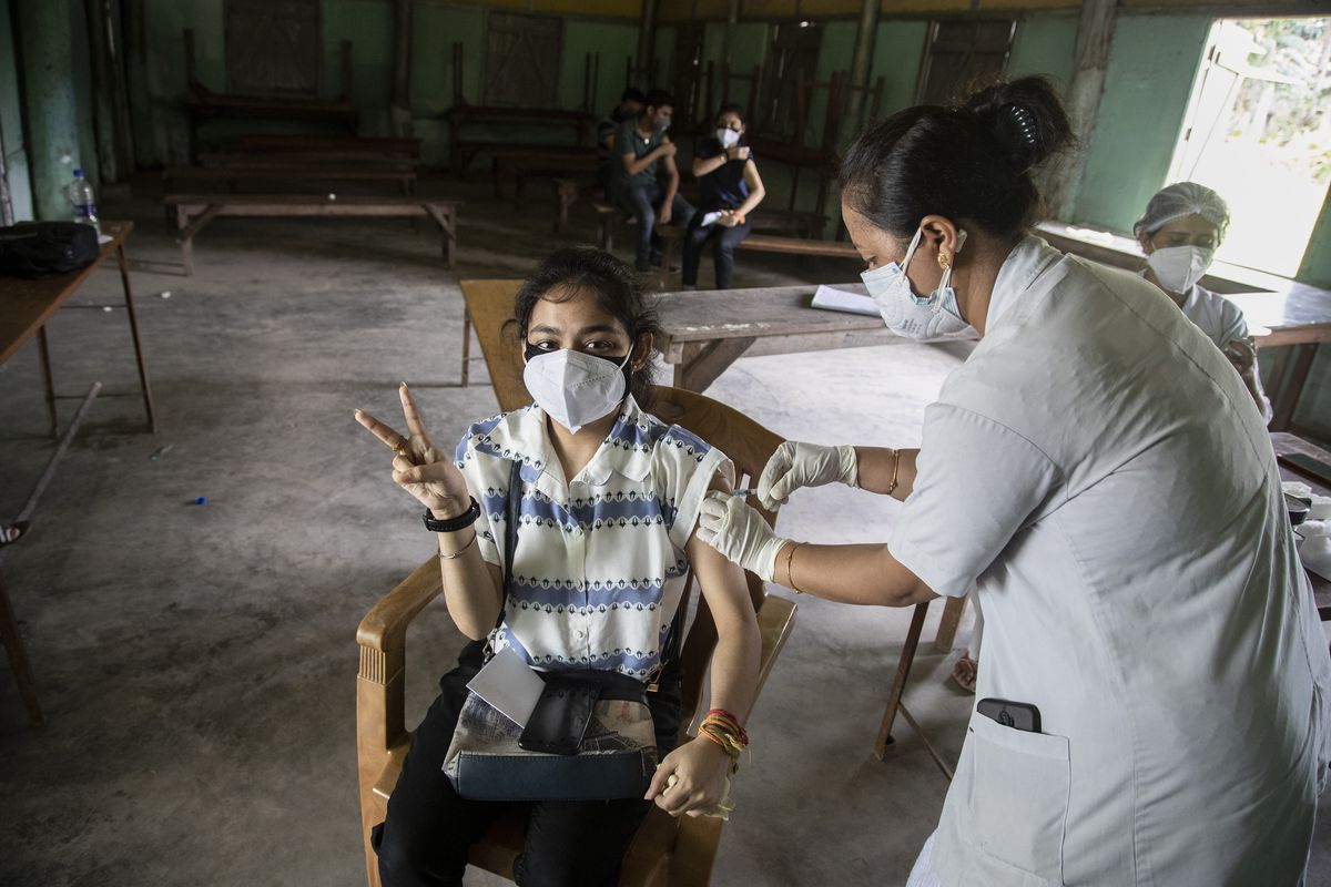 An Indian woman getting vaccinated with a dose of COVAXIN against the coronavirus gestures to camera in Gauhati, Assam, India, Monday, May 10, 2021.
