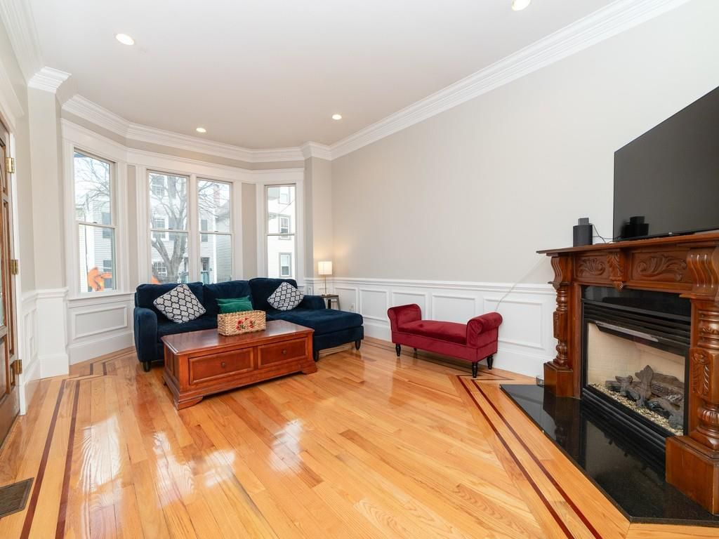 A spacious living room with a couch and a coffee table facing a fireplace.