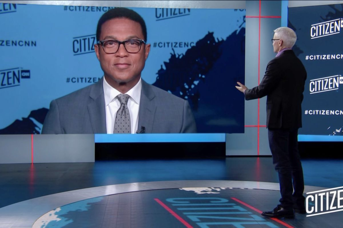 Anderson Cooper stands in the CNN studio speaking with Don Lemon, who appears on a large screen.