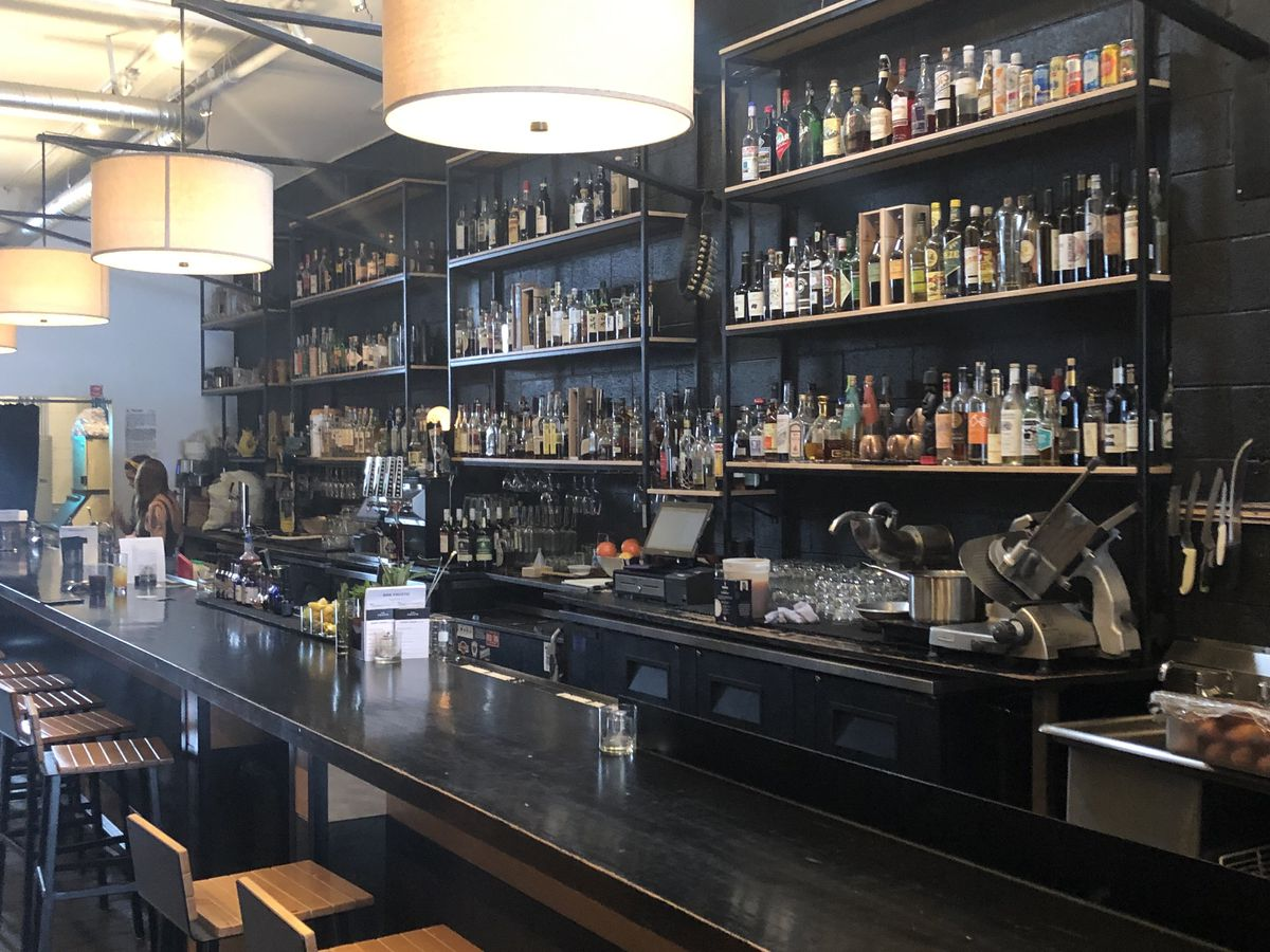 A view of wood seats facing the bar at Gold Point with three levels of shelves stocked with liquor bottles visible behind it