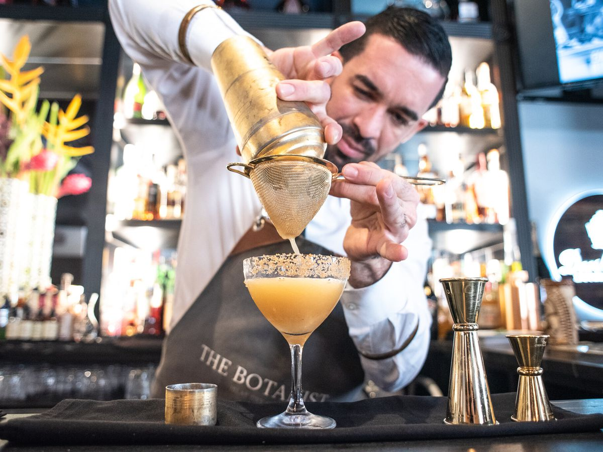 A bartender strains a shaker tin into a prepared coupe glass, in front of a brightly lit back bar full of bottles