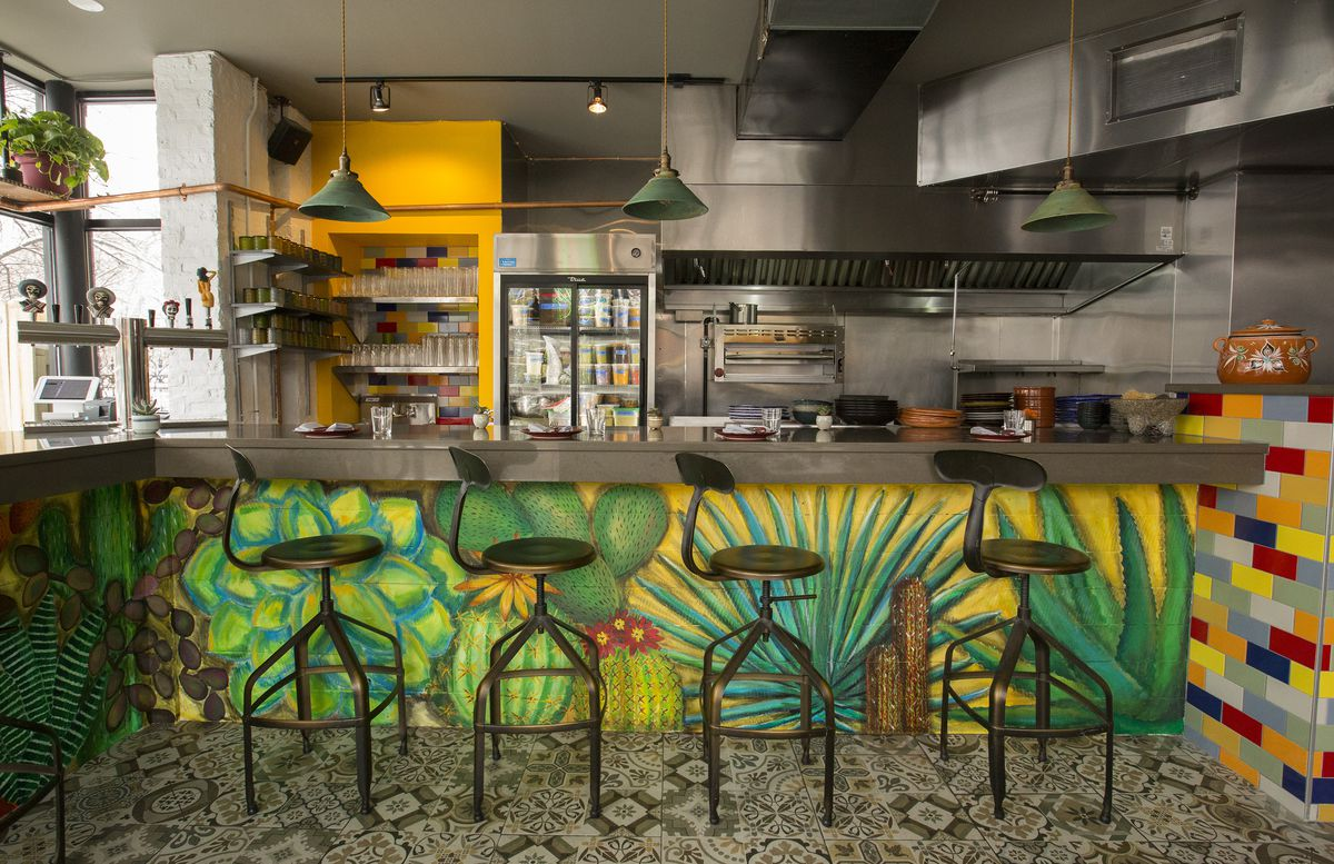 A chef's counter in front of an open kitchen painted with colorful leaves
