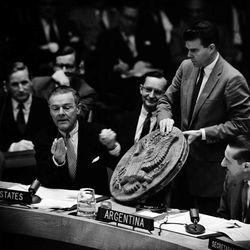 FILE - In this May 26, 1960 file photo, U.S. Ambassador to the U.N., Henry Cabot Lodge, assisted by Richard F. Pedersen, right, shows the Security Council at U.N. Headquarters a listening device which he said the Soviet authorities planted in the office of U.S. Ambassador Llewellyn Thompson in Moscow.  The device, a wooden carving of the Great Seal of the United States, was hollow and contained a hidden microphone. It was presented to Lodge by a group of Russians. Israeli Prime Minister Benjamin Netanyahu's use of a cartoon-like drawing of a bomb to convey a message over Iran's disputed nuclear program this week, follows in a long and storied tradition of leaders and diplomats using props to make their points at the United Nations.