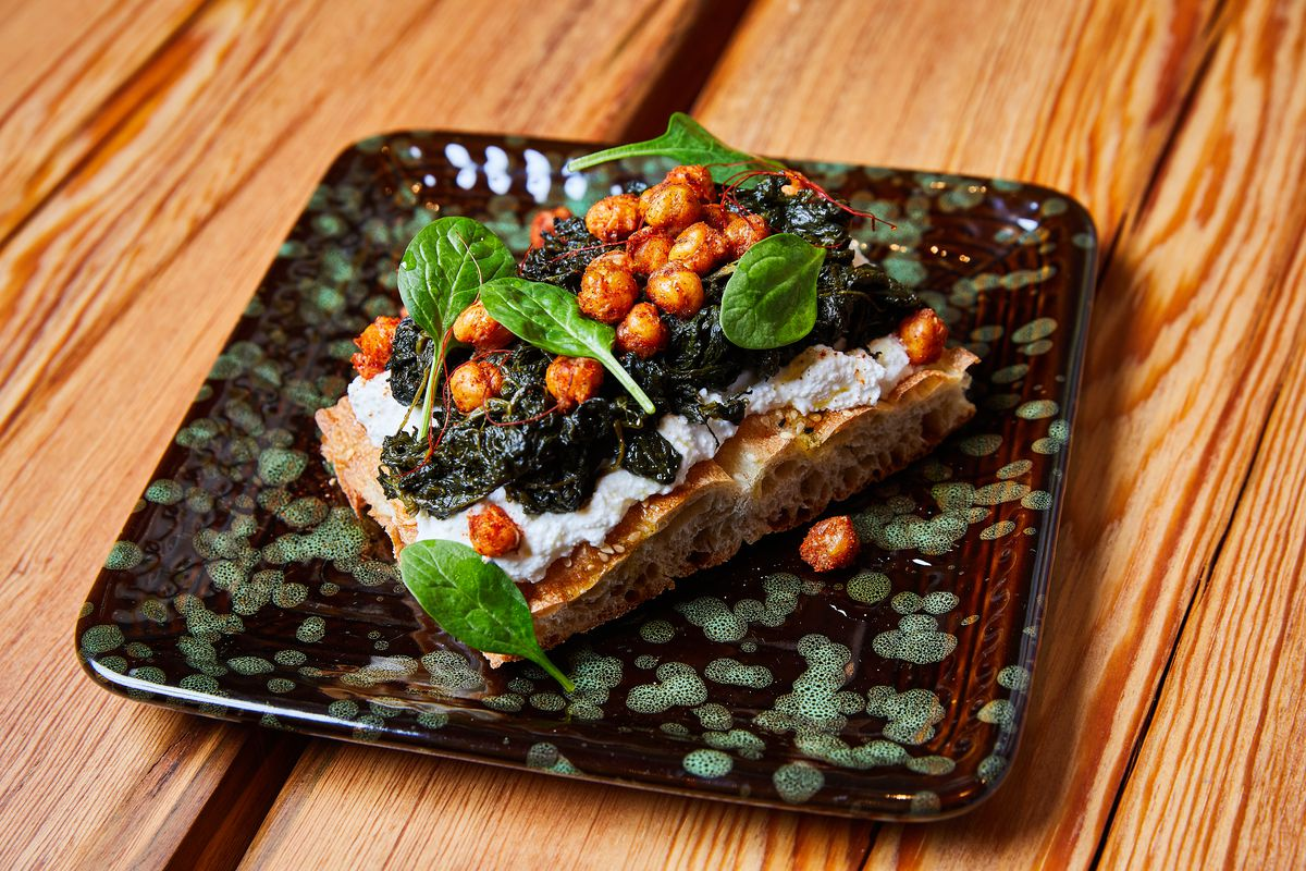 A dark patterned dish holding a square of bread with toppings set on a wooden table