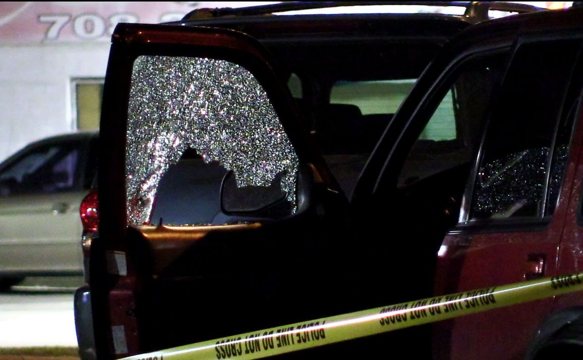 Two vehicles with shattered windows were part of a crime scene after a shooting Wednesday in south suburban Robbins.   Justin Jackson/ Sun-Times