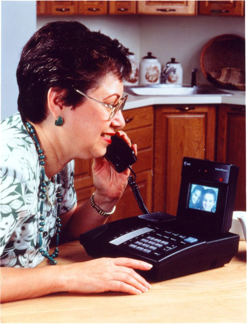 A woman talks into a video phone device.