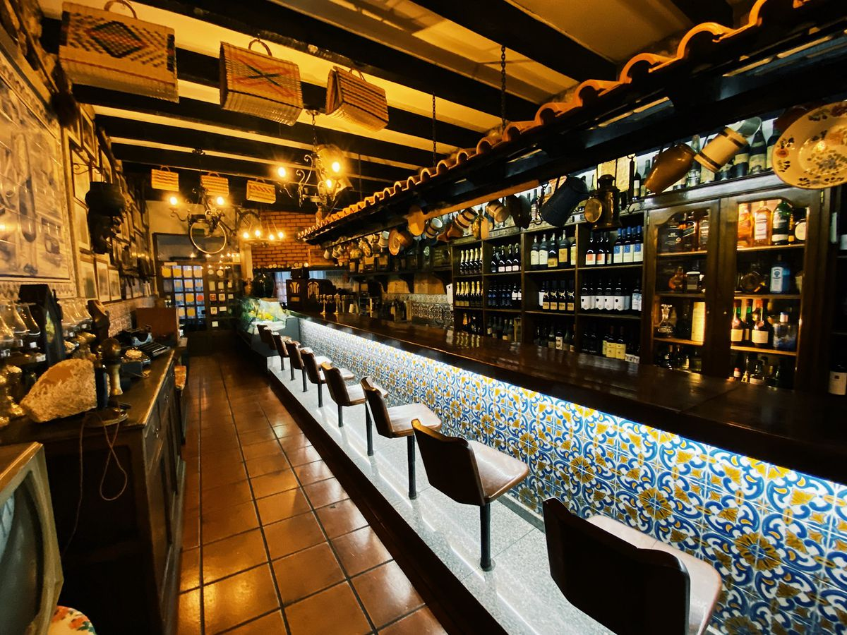 A counter with decorated illuminated tile beneath the bar and attached bar stools, a well stocked bar with pots hanging above, a tile floor, walls decorated with framed art, and baskets hanging from the exposed wood rafters