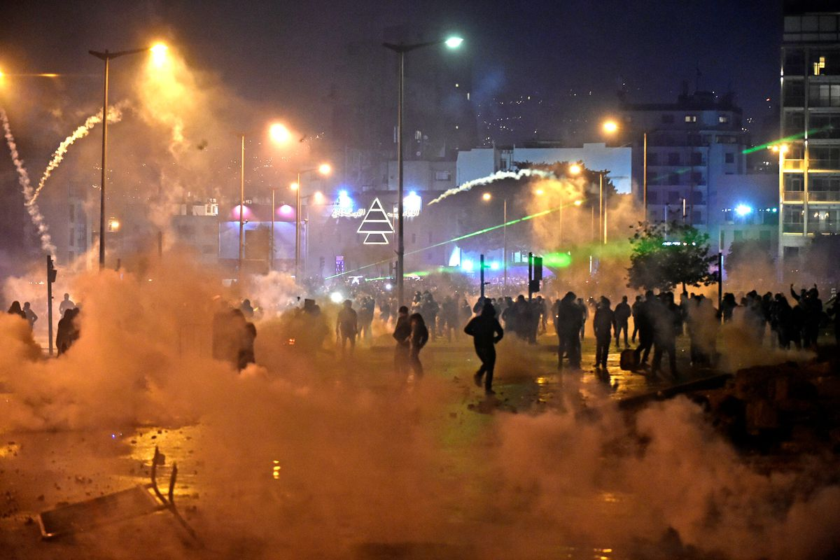 People flee through clouds of tear gas under sodium lights.