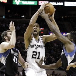 San Antonio Spurs' Tim Duncan (21) is defended by  Minnesota Timberwolves' Kevin Love (42) and Martell Webster (5) during the first quarter of an NBA basketball game on Wednesday, March 21, 2012, in San Antonio. (AP Photo/Eric Gay)
