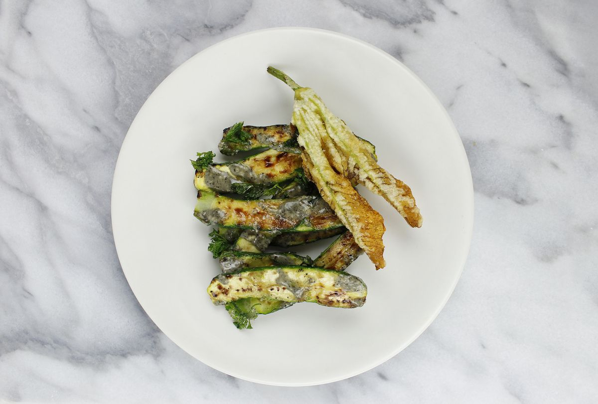 Minature green and yellow zucchini squashes cut in half lengthwise and drizzled in a black sesame dressing. Yellow fried squash blossoms are added on the side of the white plate
