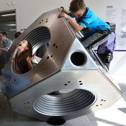 Naomi Hall and Christian Hall play on an 8-ton, solid stainless steel diamond press in the lobby of the new Tracy Hall Science Center at Weber State University in Ogden on Wednesday, Aug. 24, 2016.