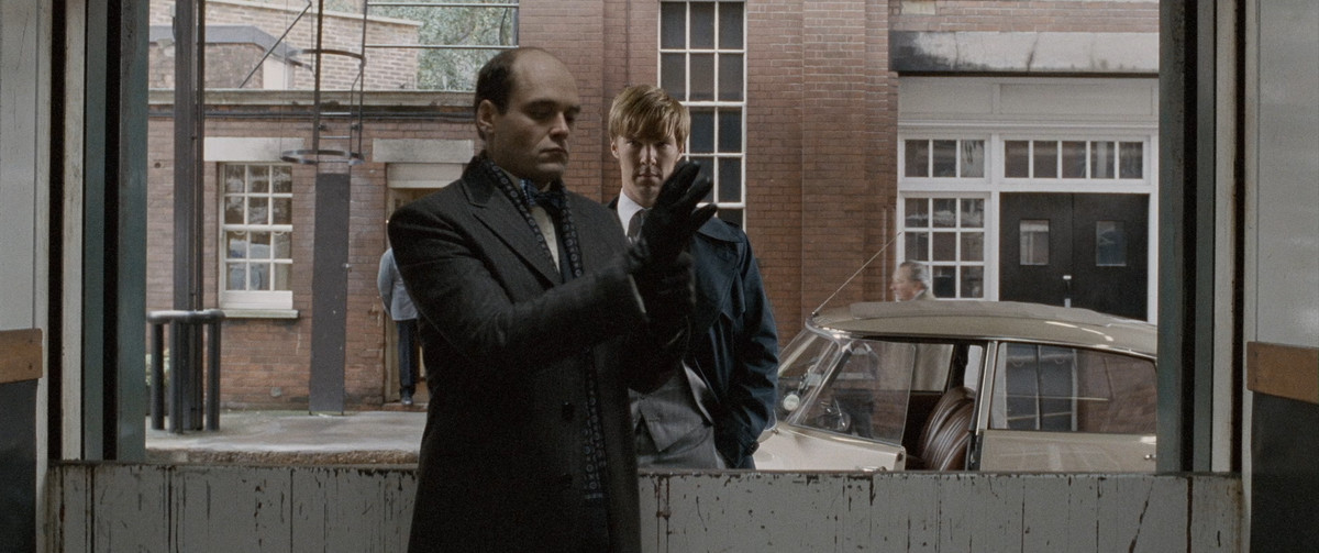 Tinker, Tailor, Soldier, Spy: Peter (benedict cumberbatch) looks through the window at a man putting on a glove
