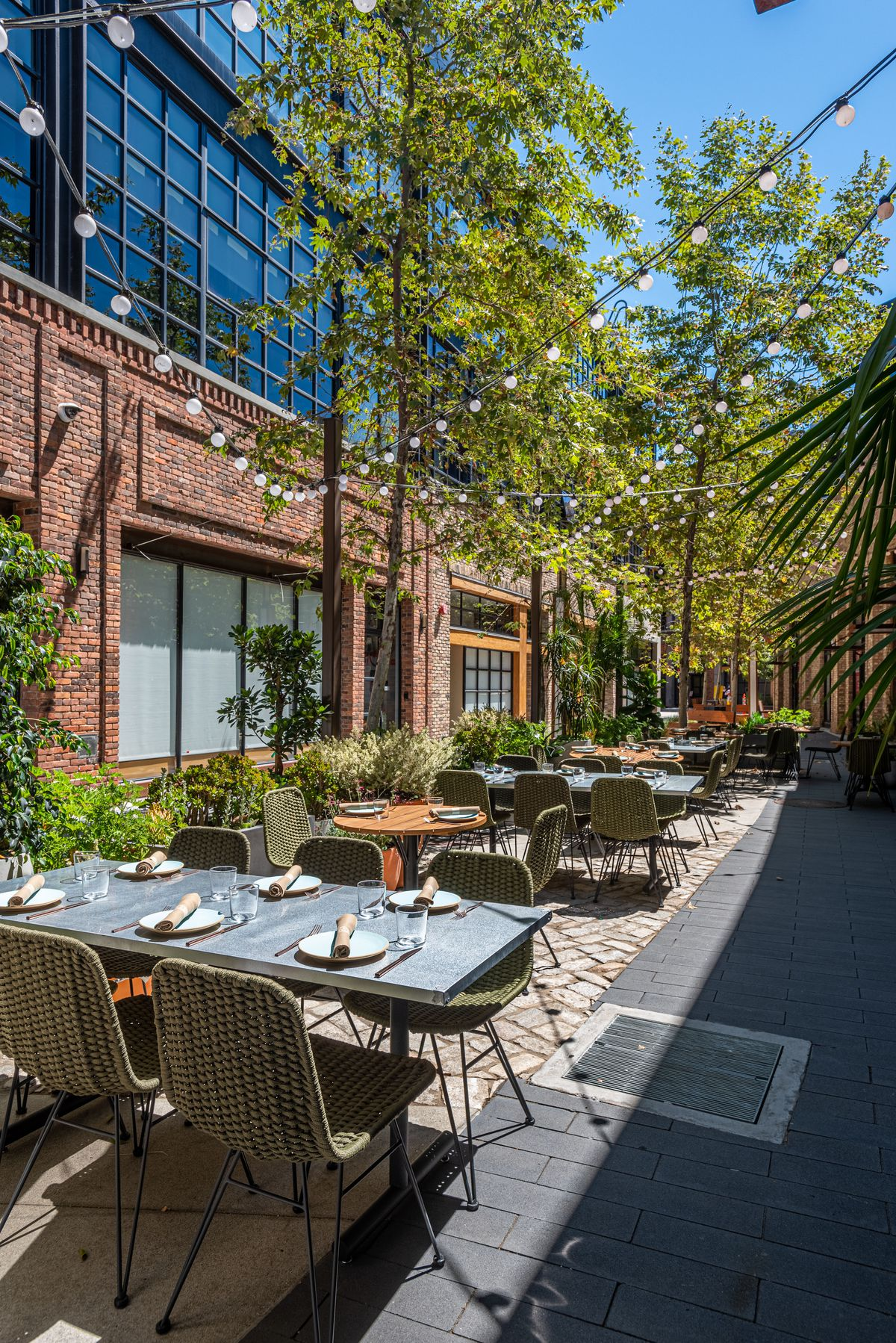 Outdoor patio seating at a new restaurant lined with brick.