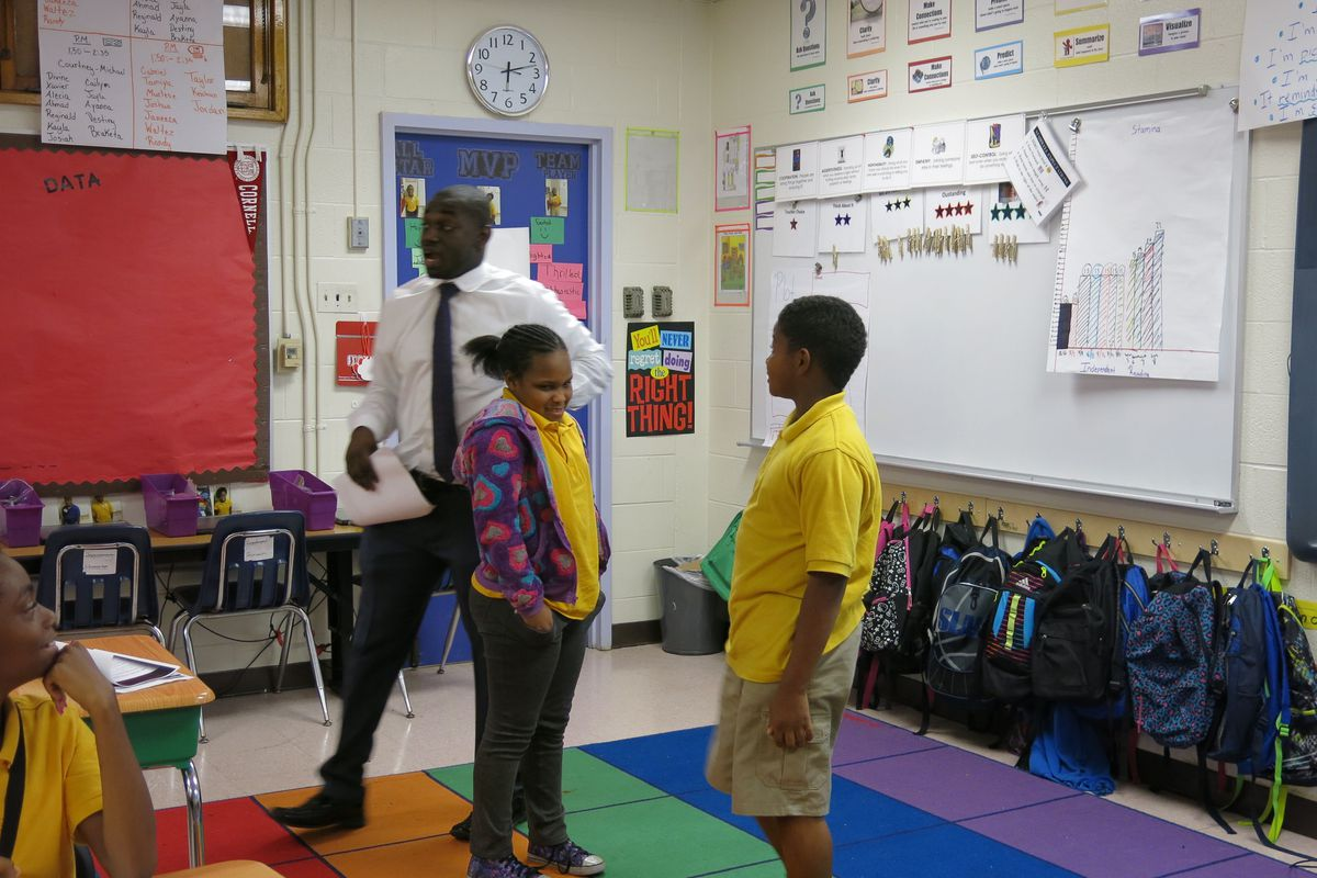 """Aspire teacher Ayo Akinmoladun picks two students to act out a scene from """"Growing Pains."""""""