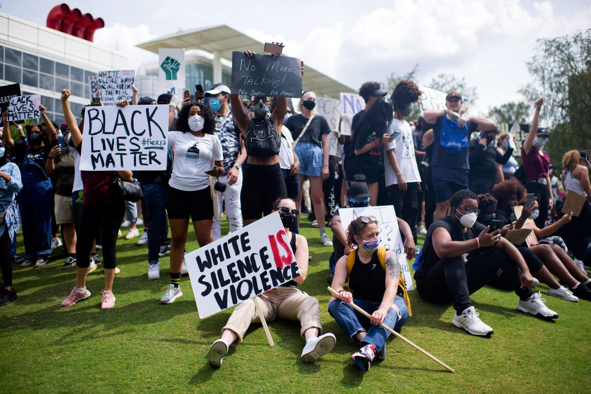 """White silence is violence"" and ""Black lives matter"" read two prominent signs."