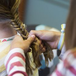 Kira O'Neil, right, braids her sister Eliza's hair as their father, CEO of the Philadelphia 76ers, Scott O'Neil visits students of the BYU Marriott School in Provo, Thursday, Oct. 13, 2016.