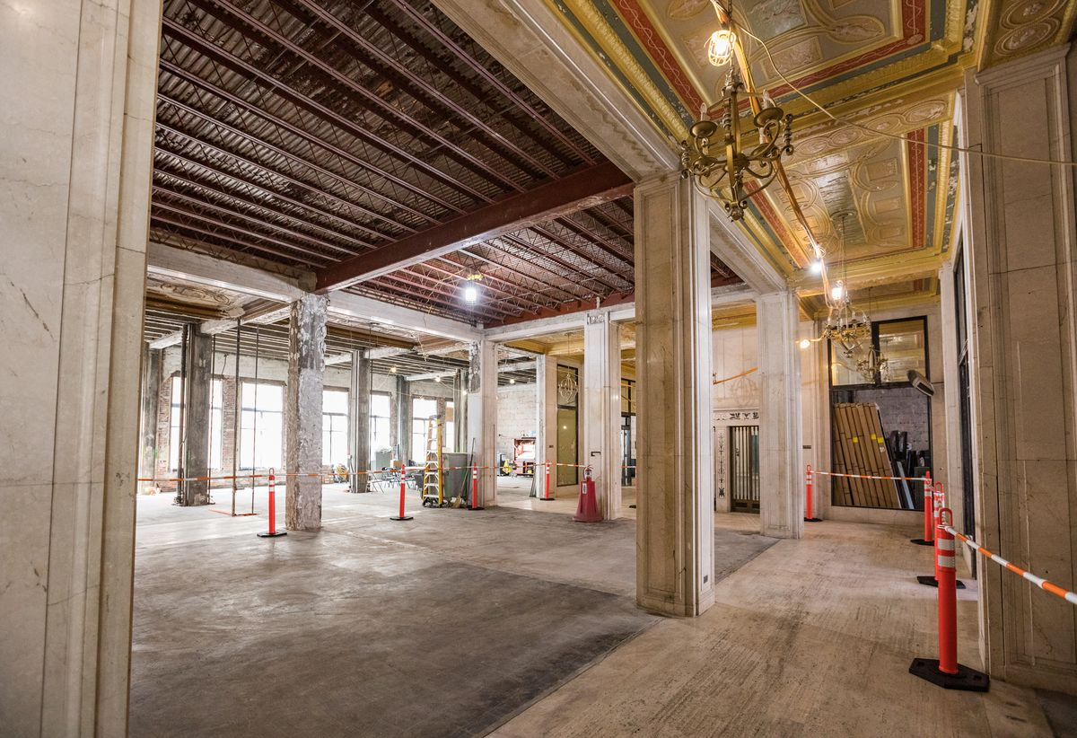 Marble columns positioned in an open space.  In addition to ornate yellow and red panels on the ceiling are exposed steel beams.