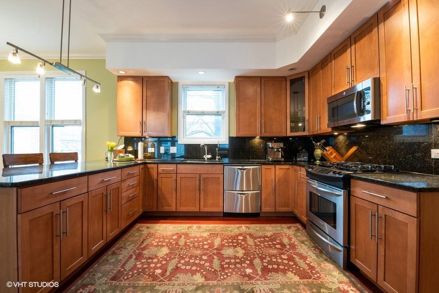 A remodeled kitchen with a large breakfast island, dark wood cabinets, and stainless steel appliances.