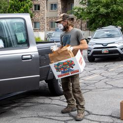 Chris Larson, left, talks with Jared Hankins, right, as customers wait in line to pick up fresh produce ordered online in Salt Lake City on Sunday, May 24, 2020. Hand Sown Homegrown Farm workers prepared the orders the day before. When customers arrived to pick up the orders, they were left in boxes by customers' cars to follow social distancing guidelines due to COVID-19.