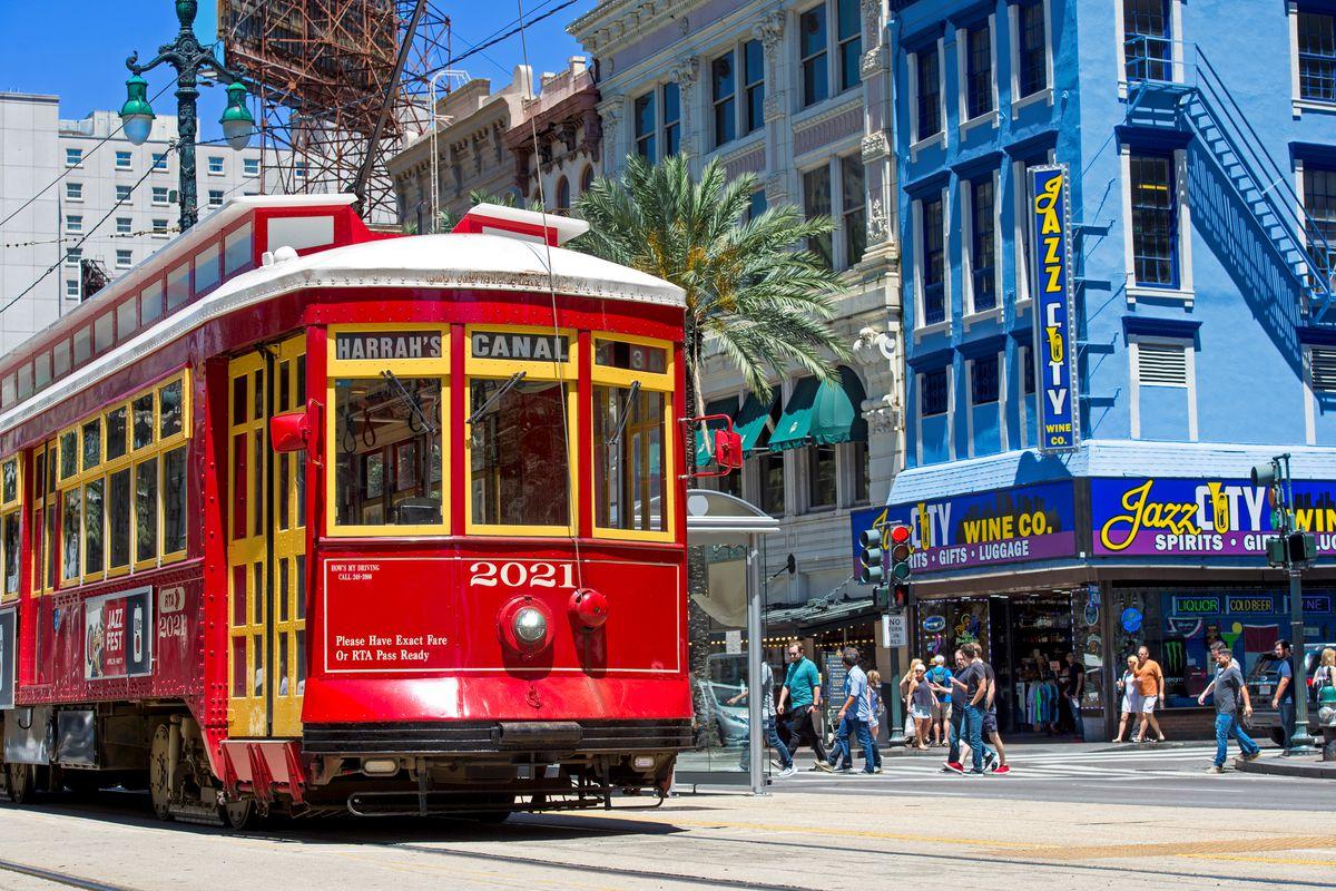 A red streetcar traverses Canal Street; pedestrians walk by a establishment advertising jazz.