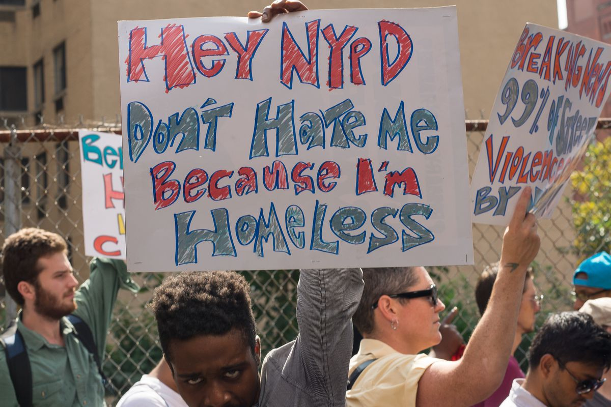 A demonstrator holds a hand-written sign at a busy rally that says: Hey NYPD don't hate me because I'm homeless.