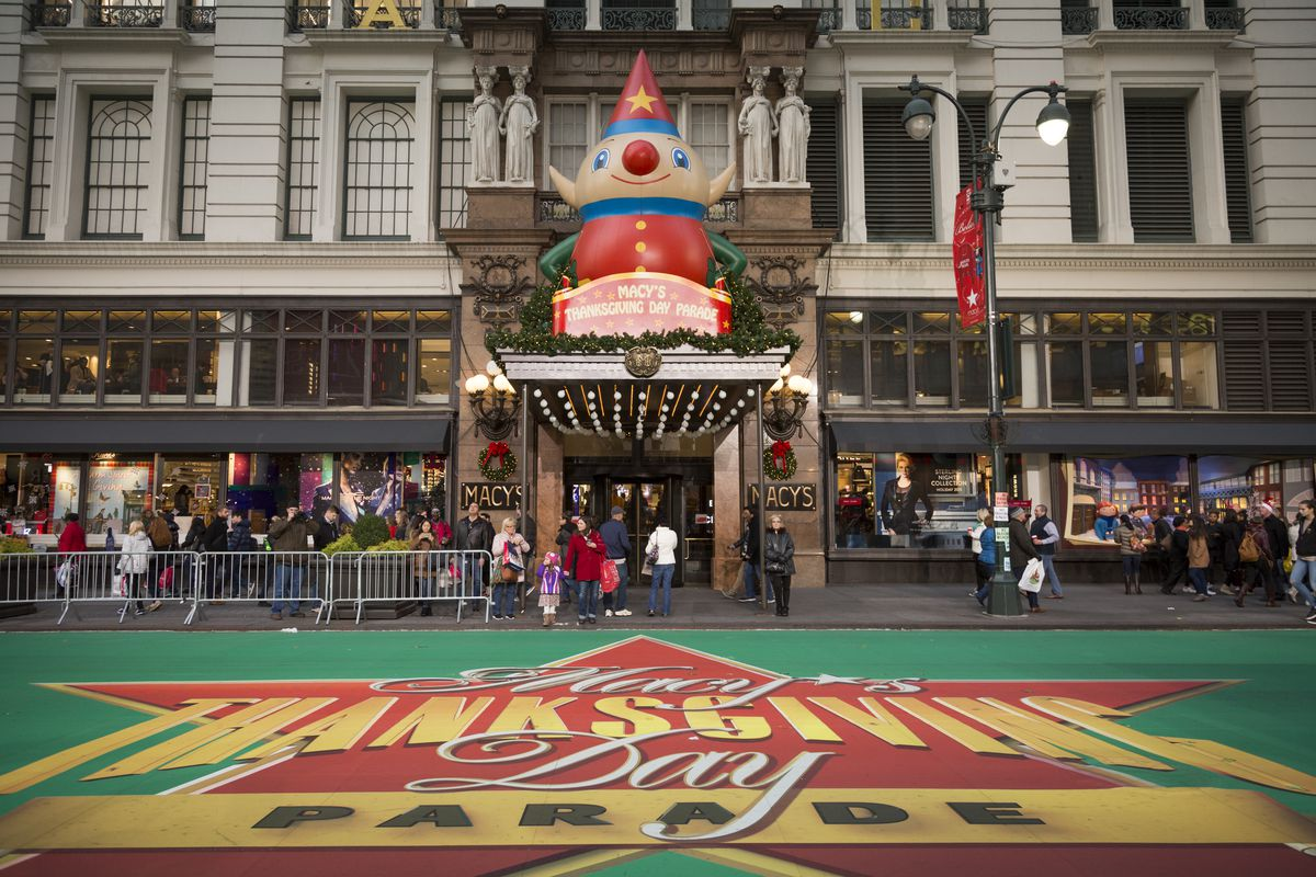 Macy's Department Store in New York City during the Macy's Thanksgiving Day Parade. There is a large sign on the street in front that reads: Macy's Thanksgiving Day Parade. There are fences along the street. People are standing behind the fences.