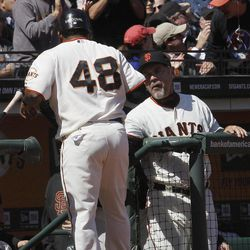 San Francisco Giants' Pablo Sandoval (48) is congratulated by manager Bruce Bochy after scoring on a single by Nate Schierholtz against the Pittsburgh Pirates during the sixth inning of a baseball game in San Francisco, Friday, April 13, 2012.