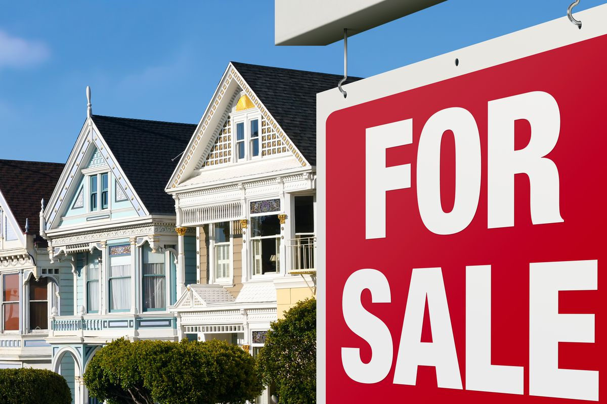 """A row of colorful Victorian homes with a red and white """"for sale"""" sign in font."""